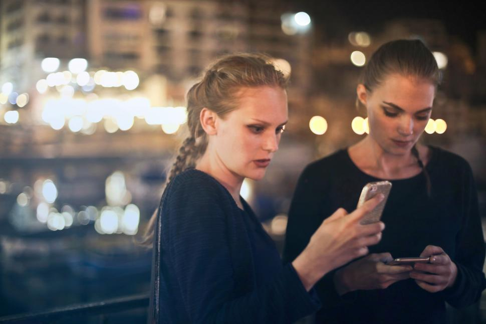 Download Free Stock HD Photo of Two young blonde women texting on their mobile phones Online